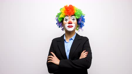 peruca : Slow motion clown with a colorful wig in business suit lookign and smiling to the camera