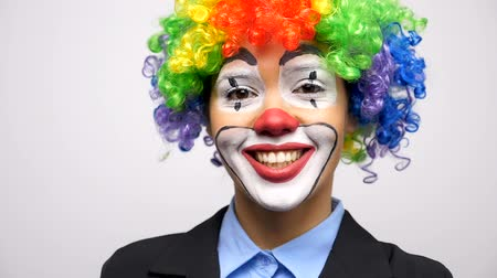 peruca : Clown wearing a colorgul wig looking and smiling at the camera