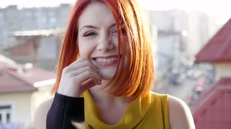 darbe : Slow motion of smiling redhead young woman on the roof of a building looking at the camera at the sunset