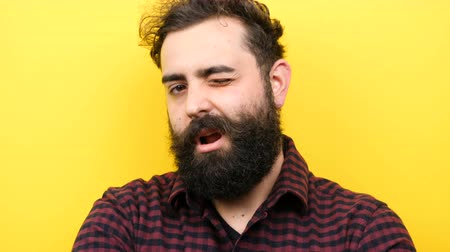 bigode : Attractive bearded man winks silly on yellow background in slow motion Stock Footage