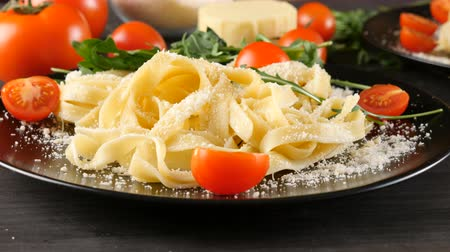 tomates cereja : Dolly paralax footage of black plate with tagliattele pasta with parmesan cheese on top Vídeos