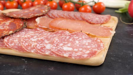 baharatlı alman sosisi : Variety of sliced italian salami on wooden board Stok Video