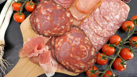 antipasti : Delicious variety of meat appetizers on wooden board. Top view Stock Footage