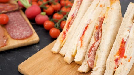 aliment : Focus tracking on club sandwich then on meat appetizers on wooden board Stock Footage