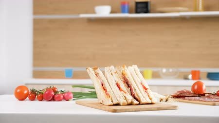 ham : Club sandwich lying on a plate in the kitchen