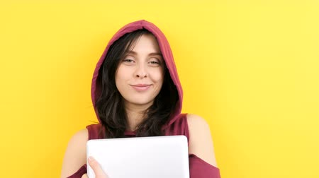 computer programmer : Young student wearing a hood and holding a laptop on yellow background in studio Stock Footage
