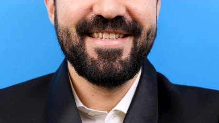 kezdet : Unrecognisable businessman smiling to the camera on blue background with perfect teeth