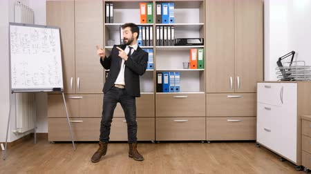 kifejező pozitivitás : Happy and successful businessman dancing in the office after long hours of work Stock mozgókép
