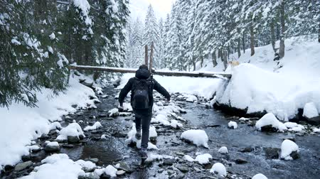 tampado : Man walking on rocks in winter river. Travel and adventure Vídeos