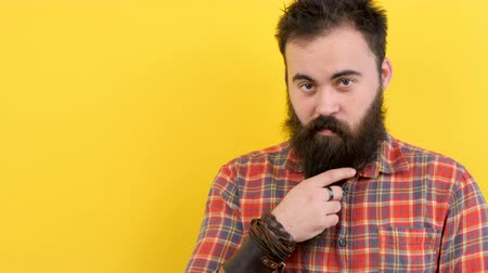 know : Cool bearded man pointing up on yellow background in studio