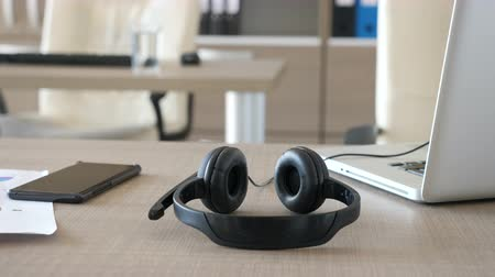interior : Parallax dolly type footage of customer care headset on a table next to a laptop and smartphone. Close up