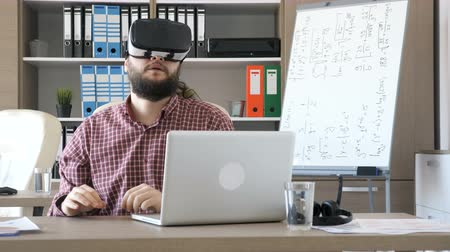 alcançando : Bearded man in an office takes VR virtual reality headset from the desk and puts it on his head. He starts touching virtual buttond and makes gestures in the air