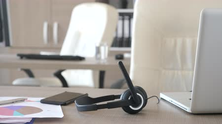 garniture : Headphones lying on the desk in customer care support office. Telemarketing or customer support line