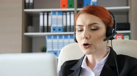 képviselő : Hotline worker at her desk looking in the laptop and speaking through headset. Customer care and help line