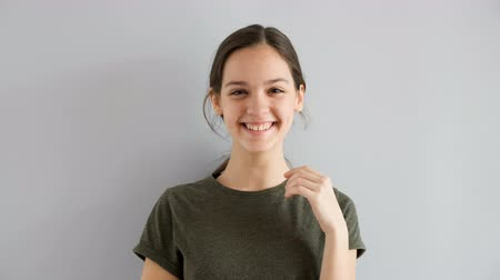 vékony : Slow motion of beautiful cute teenage girl smiling naturaly on gray background