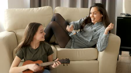 friendship dance : Two sisters are having a lot of fun in the living room. One is playing at the ukulele and the other is singing at the microphone on the sofa. Slow motion footage Stock Footage