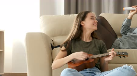 ukulele : Beautiful teenage girl playing at ukulele while her friend is singing on the couch. Girl friendship. Home and fun Stock Footage