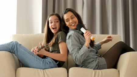 ukulele : Happy and positive sisters playing and singing on the sofa in the living room. The youngest is playing at ukulele while the oldest is singing in a microphone. They are sitting on the couch with their backs to each other
