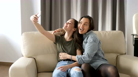 o melhor : Beautiful sisters in the living room on the couch taking a selfie. They are having fun, laughing and smiling and spending quality time together