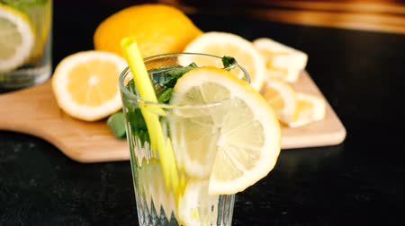 infused water : Homemade lemonade in a glass with mint on wooden board. Parallax dolly shot