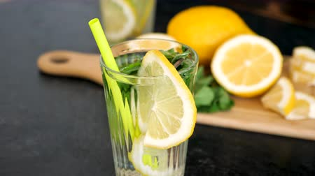 infused water : Delicious homemade lemonade with lemon and mint in a glass next to a board with lemons Stock Footage