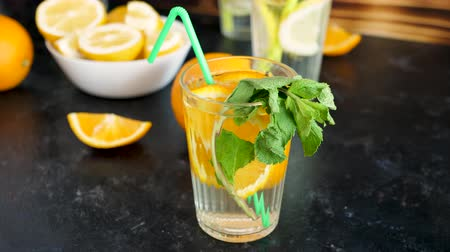 infused water : Homemade sweet and delicious orangeade with mint in a glass next to the products it was made of