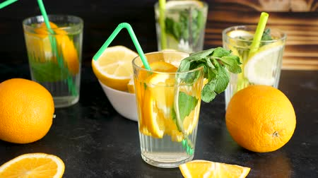 infused water : Vitamin water with slices of oranges and mint on a wooden board. Parallax dolly type footage