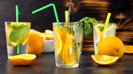 infused water : Pouring water in a glass with fresh cutted slices of oranges. Vitamin water. Slow motion footage