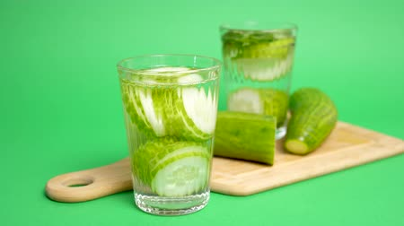 infused water : Glass with infused cucumber water next to another glass on a wooden board and cutted cucumber. Green background