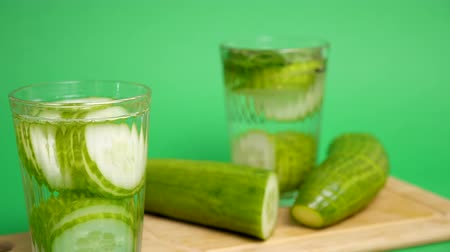 infused water : Two glasses with detox cucumber water on green background. The focus is shifting from the glass in the background to the one in the front. Dolly footage