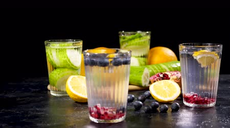 infused water : Two glasses with cucumber water and two with homemade lemonade from berries, pomegranate and lemons. Black background Stock Footage