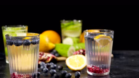 infused water : Detox water and fresh cutted fruits and vegetables next to berries on a black backgound and wooden board Stock Footage