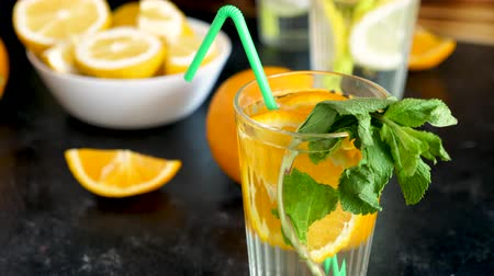 infused water : Sweet orangeade water with fresh oranges and mint on a wooden board Stock Footage