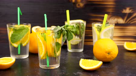 infused water : Four glasses with lemonade and orangeade on a wooden background