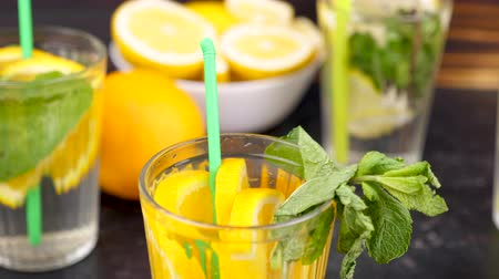 infused water : Close up of a glass with orangeade and slices of orages and mint