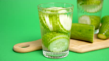 infused water : Detox water made with cucumbers on a green background