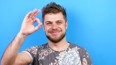 vše : Happy man smiling largely and shows OK sign to the camera. Shot on blue background. Slow motion footage. 4K resolution. Dostupné videozáznamy