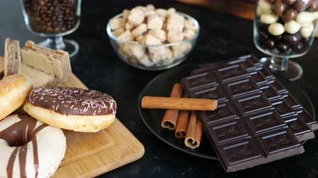 rosquinhas : Dark chocolate with cinnamon sticks on a plate next to donuts and waffles on a wooden board. Blurred in the background are a glass bowl with brown sugar and two glasses with peanuts in chocolate and coffee beans. All on a dark vintage wooden background