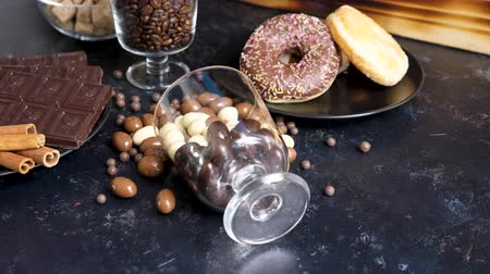 fıstık : Overturned glass with peanuts in chocolate in it on a wooden background next to other candies