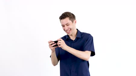 torcendo : Man in blue shirt plays video games on his smartphone over white background in studio. Slow motion footage