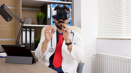 surgical equipment : Portrait of a doctor using a VR virtual reality heandset. He is in his office and wears a white robe with formal suit and red tie. Future of the medicine. Shot on motorised slider. Dolly footage