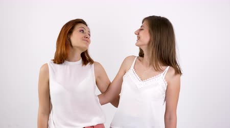 duygusallık : Two girl friends smiling each other over a white wall Stok Video