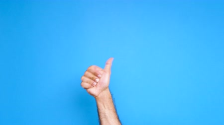 договориться : Man hand rising on blue screen and showing thumbs up sign and waiving with his fist. Close up footage