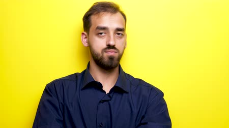 sigilo : Young beautiful man looks at his right and left them makes the silence gesture by bringing his finger to the mouth. Close up footage over yellow background