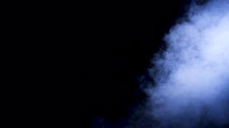 pyrotechnical : Slow motion blue smoke rising from bellow the frame over black background
