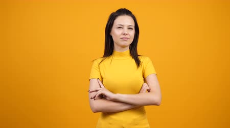インデックス : Young woman looking at her sides, puts finger to her mouth and makes the silent sign on orange background in studio. Female making silence gesture in slow motion.