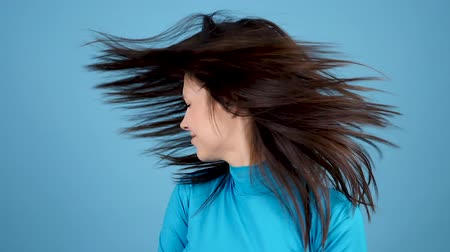 uzun saçlı : Cheerful happy girl shaking her head and the hair goes all arround on blue background. Slow motion footage