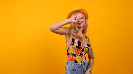 enticing : Happy sexy woman wearing sunglasses and a hat dances and smiles to the camera isolated on yellow orange background. Happines, travel, vacation and summer concept footage