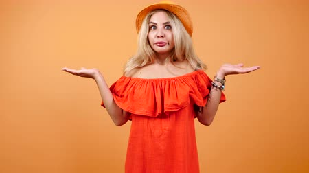 nem emberek : Blonde attractive woman wearing a summer dress and hat rises her hands up in I do not know gesture Stock mozgókép
