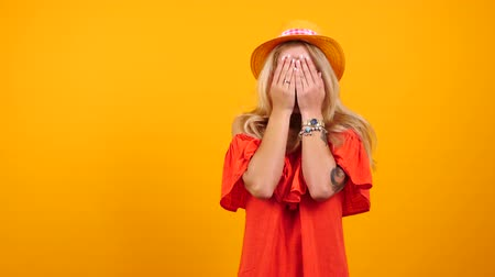 tatoo : Happy gorgeous woman covers her face and eyes from emotions and excitement on yellow orange background. Copyspace available for you text, promo, logo or advertisement